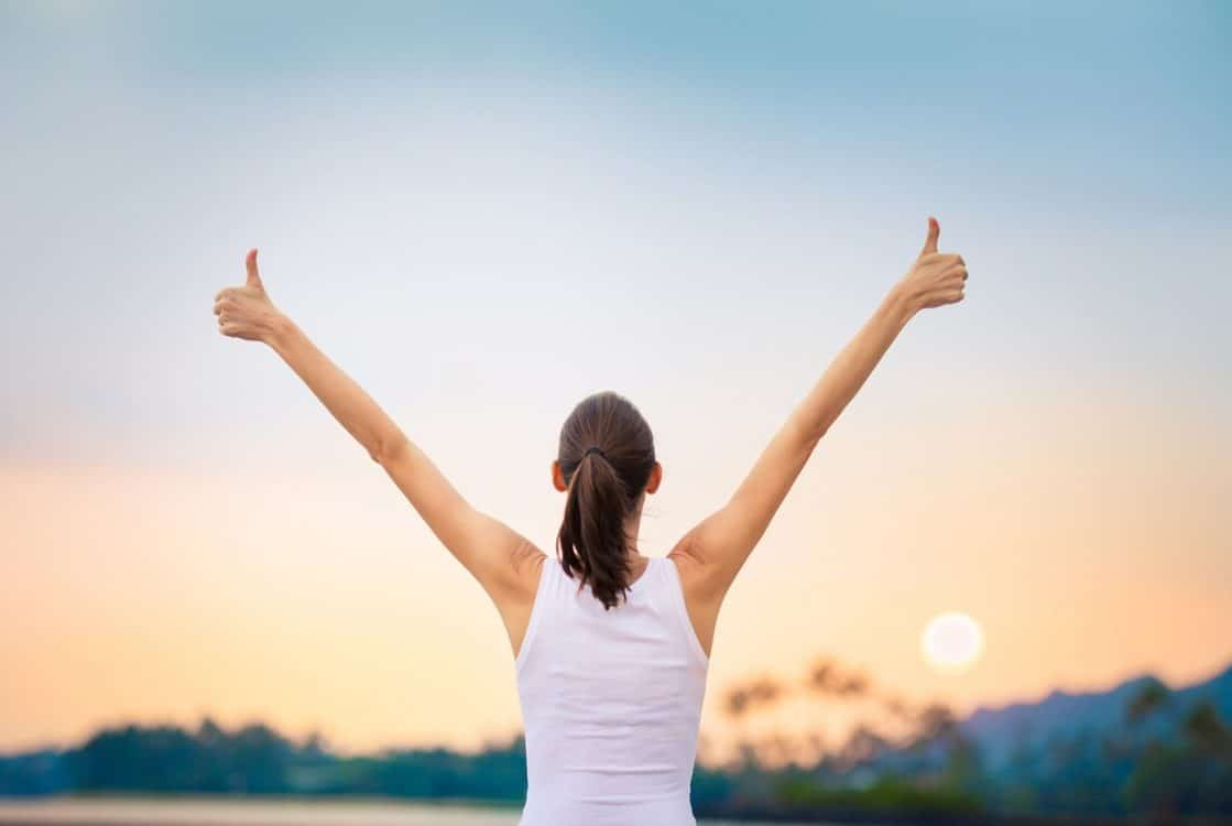 Woman with arms in the air and thumbs up