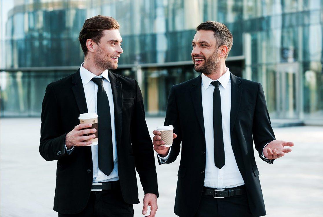 Two professional men enjoying takeaway coffee